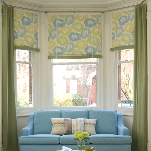Team blinds for controlling the light with dress curtains that frame the bay