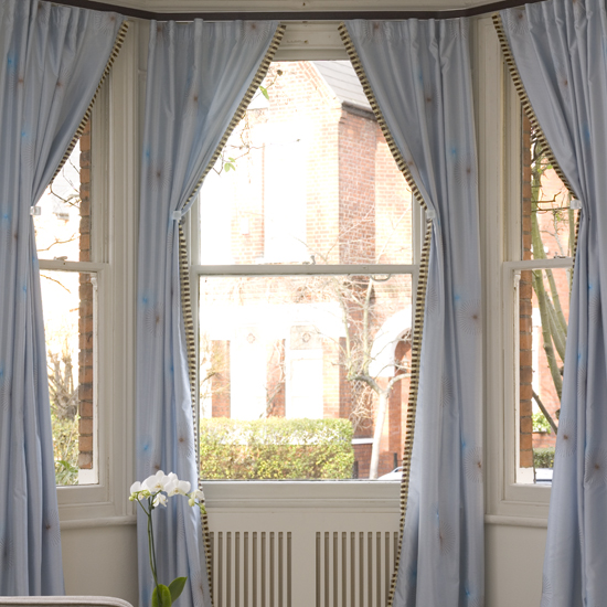 Dress up your bay window with four sweeping curtains for an elegant finish